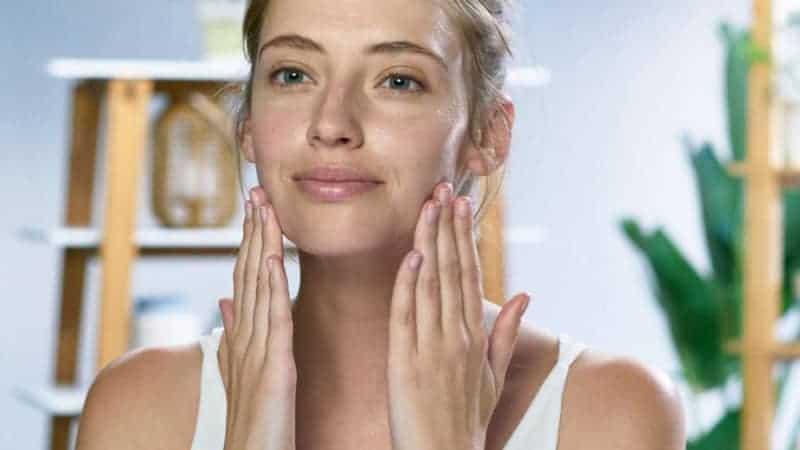 A girl massaging drugstore oil cleanser in her skin